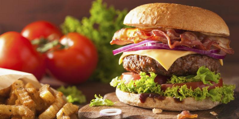 Hamburguesa con queso, bacon crujiente, cebolla caramelizada, salsa y pan tostado