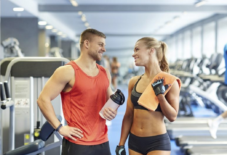 Un hombre y una mujer se sonríen en el gimnasio, instrucciones ligar en el gimnasio (IStock)