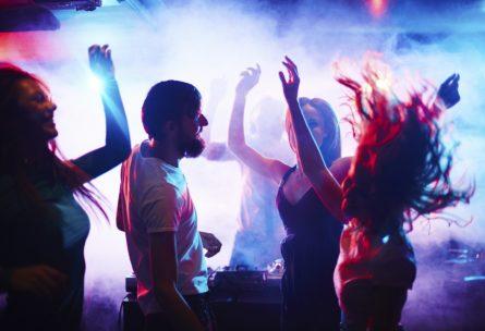 Un hombre baila con tres mujeres en una discoteca por que los tíos pagamos para entrar en la discoteca (IStock)