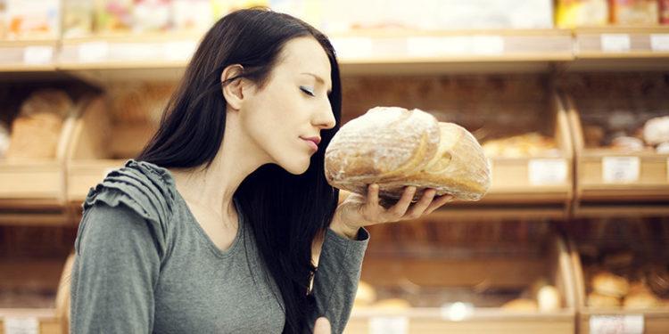 Mujer oliendo una hogaza de pan (iStock)