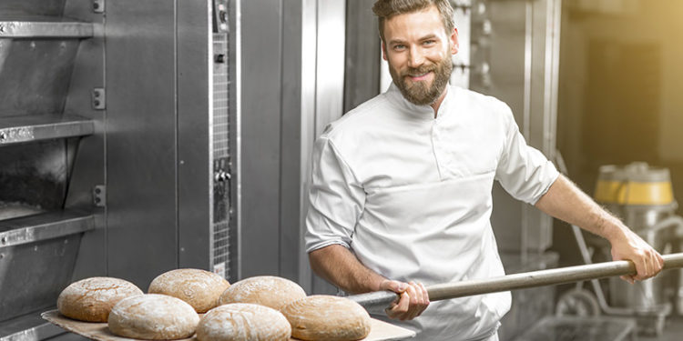 Panadero artesano sacando el pan del horno (iStock)